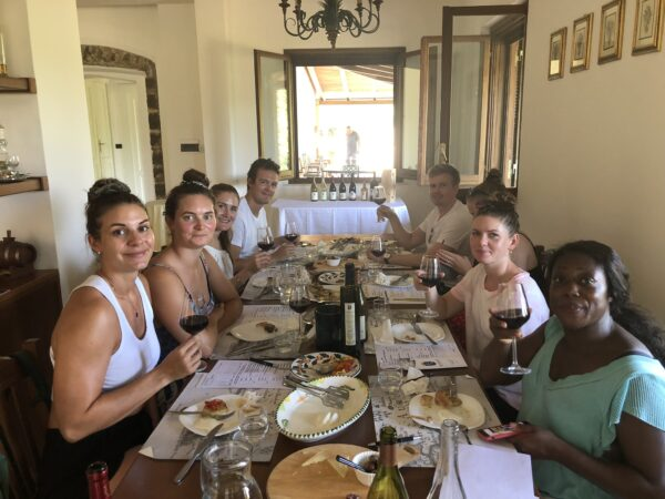 A group of people tasting wine and food at a table at Monti Cecubi winery
